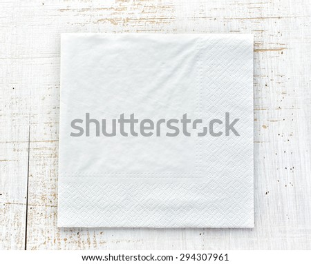 white paper napkin on wooden table - stock photo