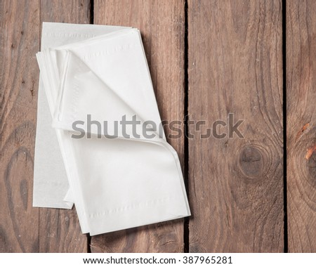White Paper Napkins on old wooden table. - stock photo