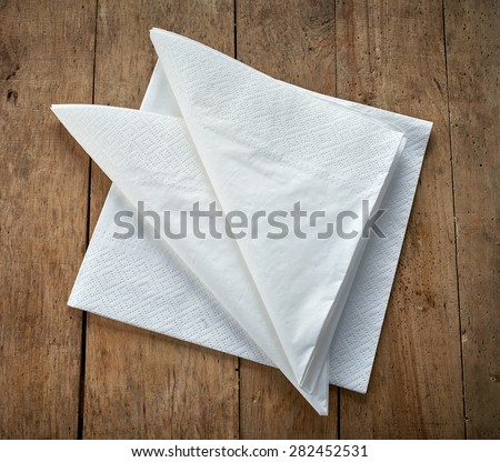 white paper napkins on wooden table - stock photo