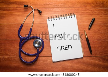 white paper of note book with black ink pen and stethoscope on wooden table, written I AM TIRED - stock photo