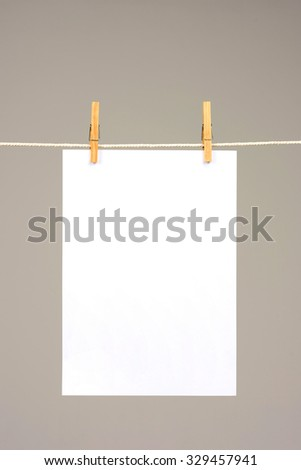 White paper on washing line on silver background