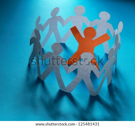 White paper people standing in a cycle and one orange paper man inside - stock photo
