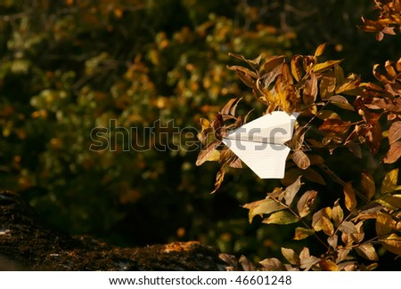 White paper plane get stuck in branches - stock photo