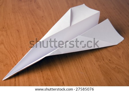 white paper plane on table - stock photo