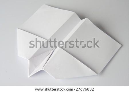 white paper plane on white background - stock photo