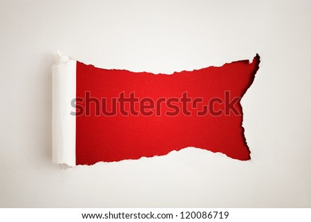 White paper torn to reveal red panel ideal for copy space - stock photo