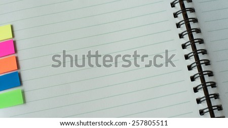 White paper with blank space and color post it on notebook