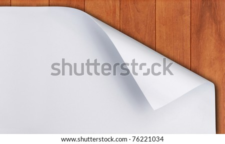 White paper with corner curl over wooden background - stock photo