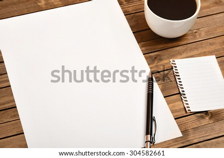 White paper with cup of coffee on wooden table - stock photo