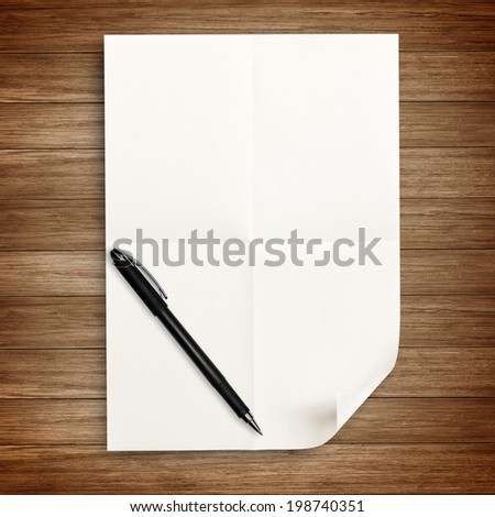 white paper with pen isolated on wood - stock photo