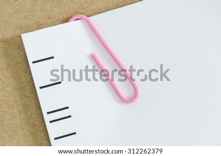 White paper with pink paper clip   on brown paper background. - stock photo
