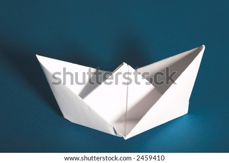 white paper yacht with shadow on blue background