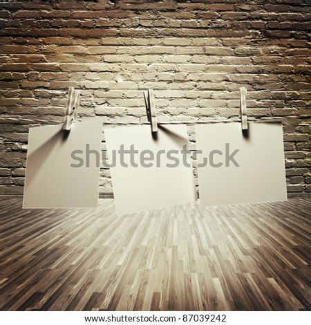 white papers attach to rope with clothes pins on brick wall background - stock photo