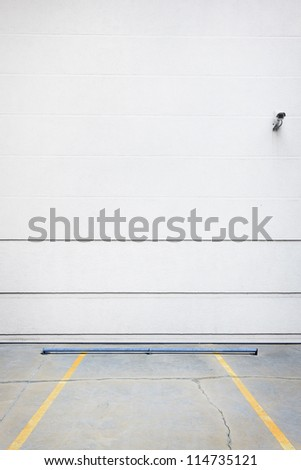 White parking wall with security camera