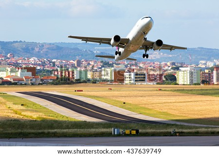 White passenger airplane is take-off from airport runaway. Aircraft flies against a background of city residential areas. - stock photo