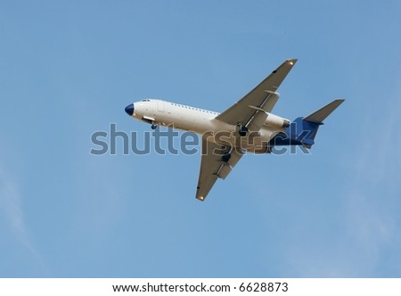 White passenger airplane landing against clear blue sky - stock photo