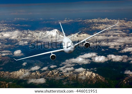 White passenger jet airplane with left roll. Aircraft is flying in the blue sky over the clouds and mountains. - stock photo