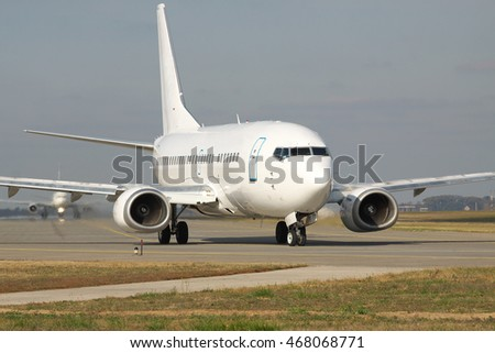 White passenger jet plane is taxiing to the runway in the airport on sunny day