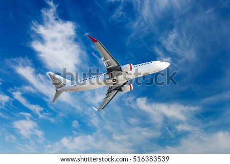 White passenger plane in flight. Aircraft flies against a background of bright blue cirrus clouds.