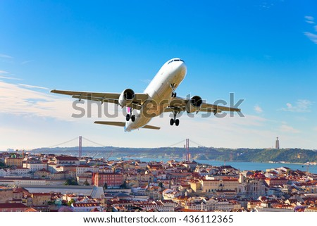 White passenger plane is flying in the blue sky over the city rooftops, river and bridge - stock photo