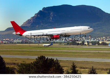 White passenger plane with a red tail. Aircraft is arriving at the airport. In the background is a huge mountain. - stock photo