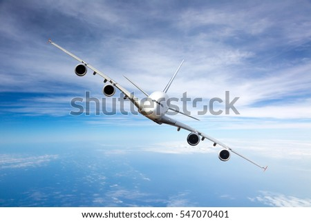 White passenger plane with right roll. Aircraft flying high in the blue cloudy sky. Airplane front view.
