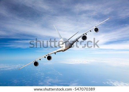 White passenger wide body aircraft with left roll. Plane flying high in the blue cloudy sky. Airplane front view.