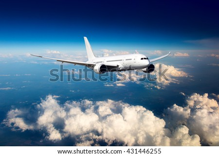 White passenger wide-body airplane. Aircraft is flying in the blue sky over the the clouds. - stock photo