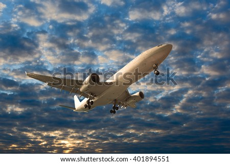 White passenger wide-body plane. Aircraft is flying in blue cloudy sunset sky. - stock photo