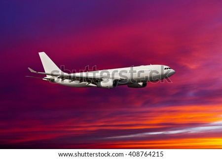 White passenger wide-body plane. Aircraft is flying in the sunset sky. - stock photo