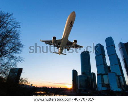 White passenger wide-body plane. Aircraft is flying in the sunset sky over the river and skyscrapers. - stock photo