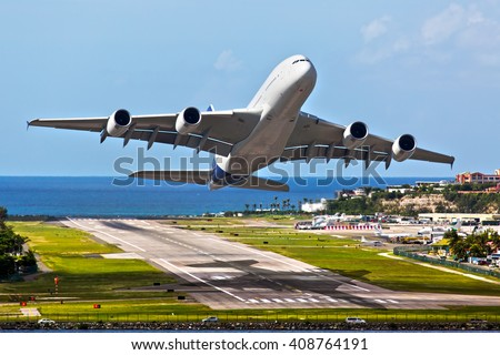 White passenger wide-body plane. Aircraft takes off from the airport runway on the sea background.
