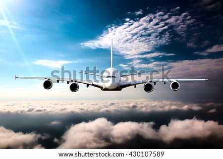 White passenger wide-body plane in horizontal flight. Aircraft is flying in the blue sky over the the clouds. - stock photo