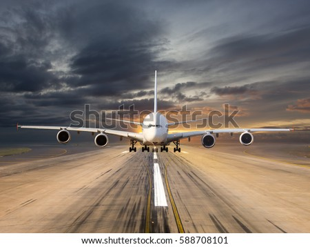 White passenger wide-body plane takes off from the airport runway. Aircraft moves against the backdrop of sunset sky. Airplane front view.