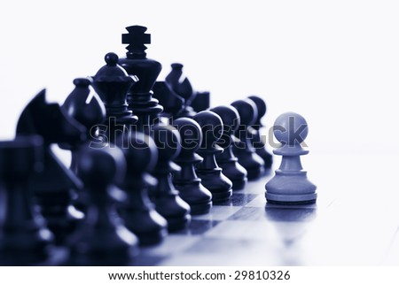 White pawn challenging black chess pieces - stock photo