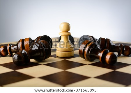 White pawn surrounded by black pawns on a chessboard