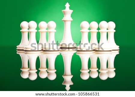 white pawns protecting their leader, the white king - chess pieces on green background - stock photo