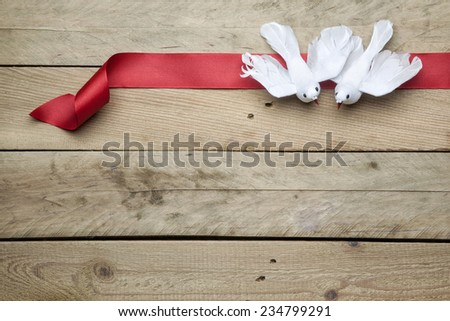 White peace doves on red ribbon and wooden background - stock photo