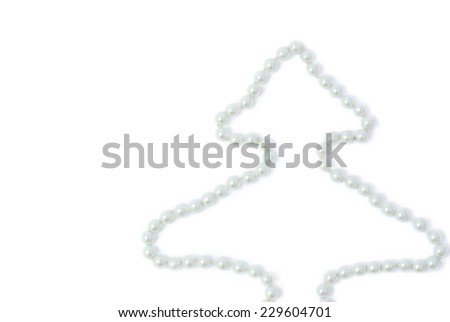 White pearls on a white background in the form of spruce - stock photo