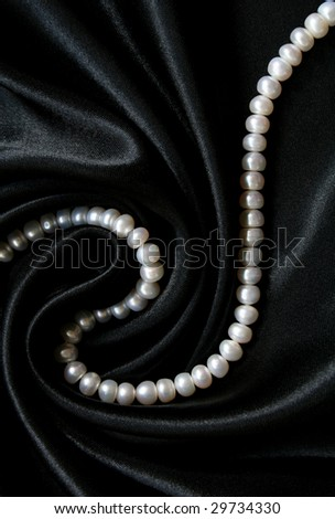 White pearls on the black silk can use as background - stock photo