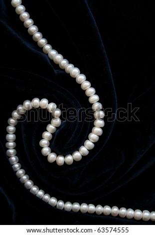 White pearls on the black velvet as background - stock photo