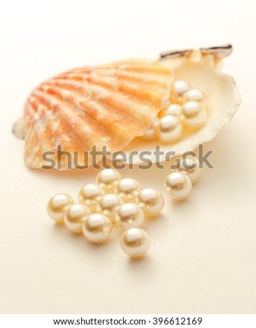 White pearls scattering out of seashell closeup - stock photo