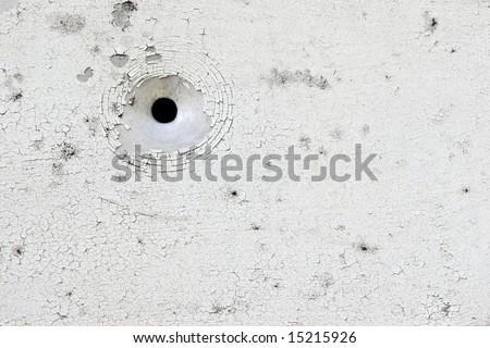 White peeling paint aluminium plate with bullet hole - stock photo