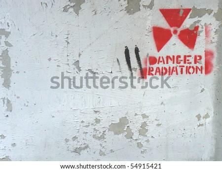 white peeling paint on wall with radiation warning - stock photo