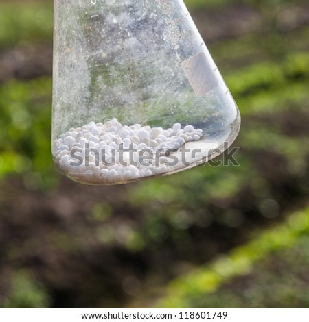 white pellet chemical fertilizer in the flask in the field - stock photo