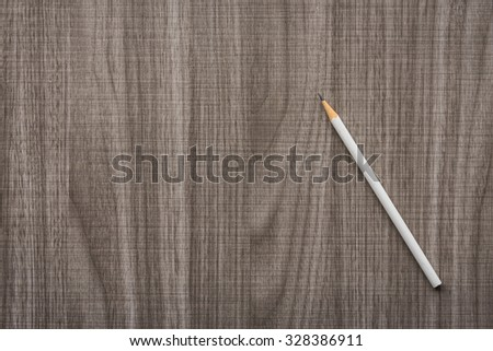 white pencil on wooden table - stock photo