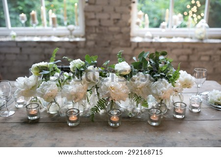 white peonies are in glass bottles next to the candles on vintage wooden table in the loft - stock photo