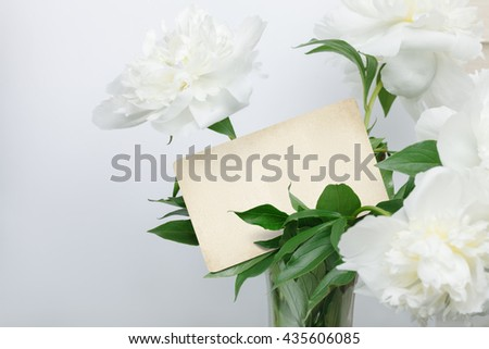White peonies bouquet with retro blank card inside. Ready for your text. - stock photo