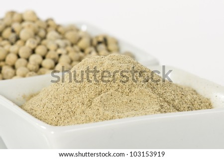 White pepper grain and powder on ceramic bowl - stock photo