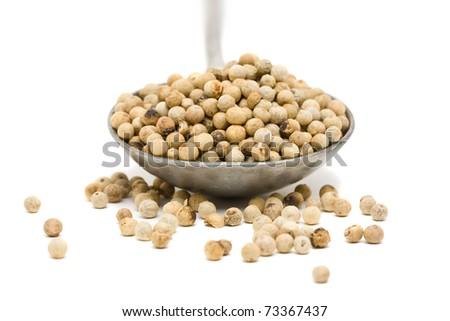 White peppercorns on metal spoon over white background - stock photo